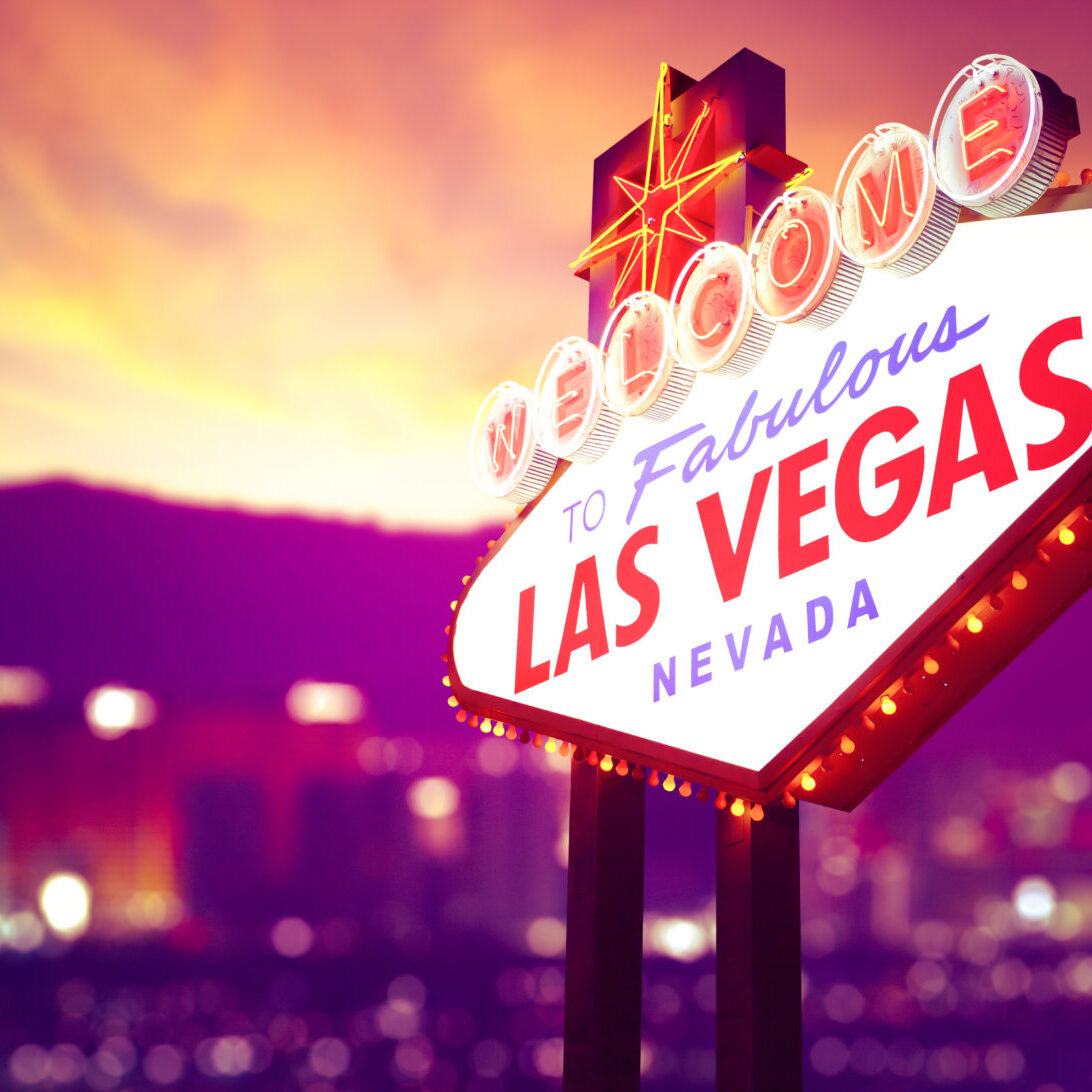 Welcome To Fabulous Las Vegas Sign On A Bokeh Background Of The Las Vegas Strip At Sunset. The bright lights of the Las Vegas Strip can be seen in the background. Las Vegas is an internationally renowned major resort city and tourist destination known primarily for gambling, shopping, fine dining.